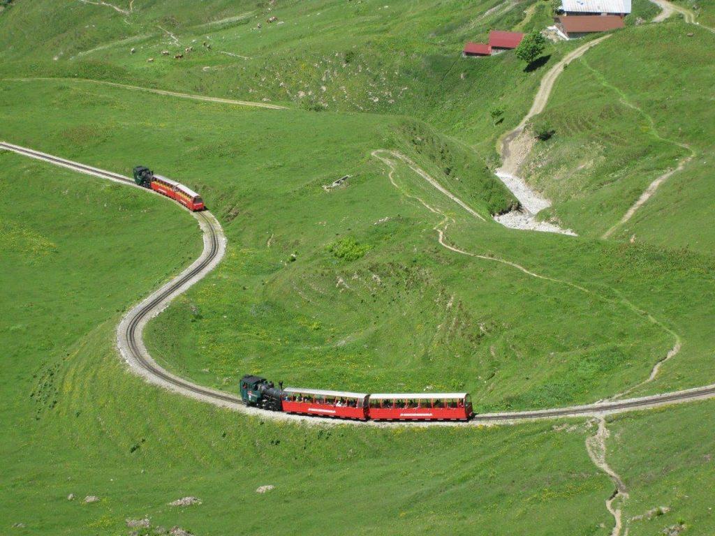 Zwei von den neuen Zahnraddampflokomotiven geschobene Personenzüge auf Bergfahrt. Die Züge verkehren auf Sicht und folgen sich in kurzen Abständen. Foto Roger Waller