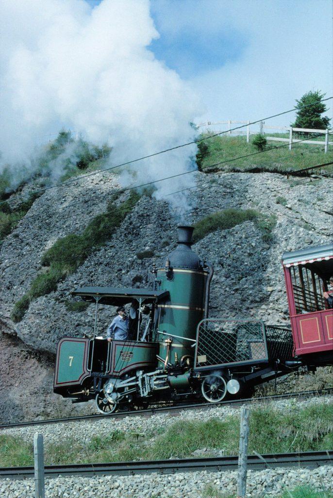 Für das 125-Jahr-Jubiläum der SLM und der Rigibahn wurde die ursprünglich 1873 von der SLM erbaute Zahnrad-Dampflokomotive H 1/2 Nr. 7 betriebsfähig revidiert. Dies bedingte einen neuen, geschweissten Kessel mit neuen Sicherheitsventilen. Um die heutigen Weichen zu befahren, war zudem ein neu entwickelter Antrieb erforderlich, der direkt auf das Triebzahnrad wirkt. Wegen der Fahrleitung musste  ein neues, kürzeres Kamin mit einem Lempor-Blasrohr eingebaut werden. Das Bild zeigt die Lokomotive mit Volldampf unterwegs von Rigi Staffel zum Rigi Kulm. Foto Roger Waller